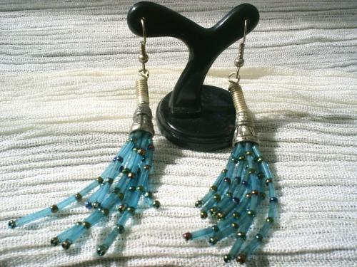 TENTACULES:Boucles d'oreille pour oreille percée, fermoir argenté, cloche en métal argenté de type indien, rocailles de forme tube bleues transparent séparées par des rocailles multicolore.
