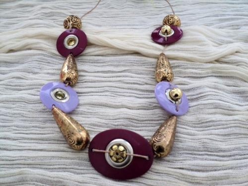 BOUTON D'OR:Sautoir sur cordon en coton ciré beige, enfilade de perles en plastique dure, ovales et rondes, mauve et prune.Le centre de chaque perle a un entourage en métal argenté, une perle en métal doré remplit ce centre. Chaque perle en plastique est séparée de la suivante par des perles allongées et dorées, martelées à l'ancienne et 2 perles rondes du même métal finissant l'enfilade. Vous pouvez mettre ce collier à la hauteur que vous désirez. Le plus de ce collier est d'avoir marié des perles modernes et des perles anciennes