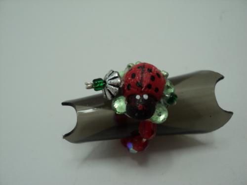 P'TIT COCCINELLE:Bague sur anneau �lastique.Support d�cor� par une coccinelle en bois,de 4 petits strass verts, de rocaille verte et surmont�e d'une petite fleur en m�tal argent� ayant en son milieu une rocaille verte. L'anneau �lastique est en perles facette rouges, et r�glable � tous les doigts de petite fille.