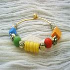 MARIE: Bracelet en fil d'aluminium doré, sur le quel sont enfilés des perles en bois multicolore et perles en métal doré.