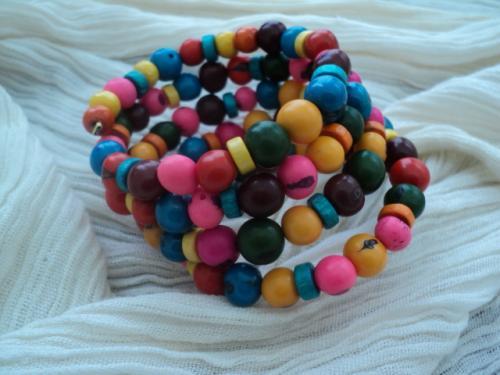 ACAÎ:Bracelet mémoire de 5 rangs multicolore composé de perles açaÏ* et d'intercalaires en bois. Ce bracelet égayera votre vie et vos tenues de printemps et d'été. S'adapte à tous les poignets  *La perle açaï est en fait le fruit d'un palmier couleur marron, mais on la trouve teintée de toutes les couleurs