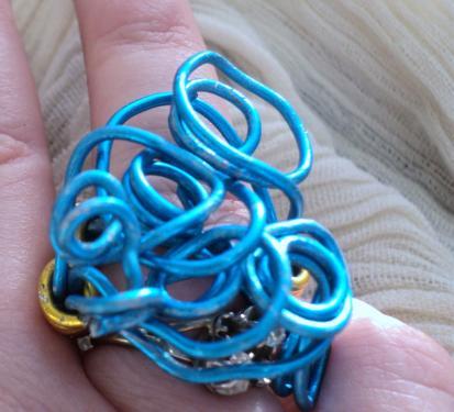 Bague en fil d'aluminium bleu formant un tortillon et se prolonge pour faire l'anneau pour une bague réglable,les rangs de l