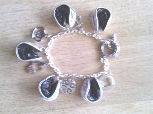 Bracelet chaîne argentée, breloques et capsules écrasées noires.