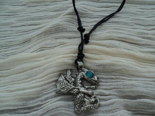 Dragon bleu: Pendentif en métal argenté, petit strass bleu à l'oeil . Le pendentif est fourni avec un lien en coton noir, réglable.  Ce bijou fait parti de la série des bijoux relookés.