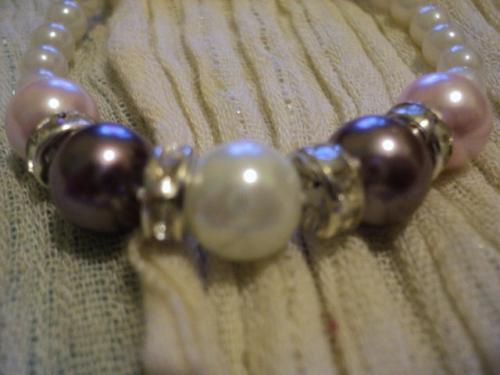Bracelet élastique en perles de nacre blanches, roses et violettes séparées par des anneaux strass transparent. Le reste du bracelet est composé de perles de nacre blanches.