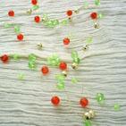 FROU-FROU:Collier en fil d'aluminium doré torsadé et parcouru par des perles de verre rouge et vert et perles métallique dorée;Ce collier peu prendre n'importe quel forme grâce au fil .