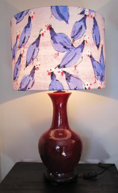 Lampe en céramique dans les tons rouge carmin et abat-jour cylindrique en tissu Lalie Design.