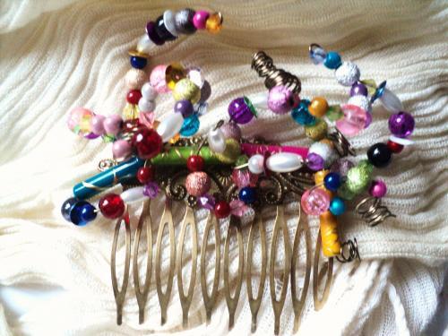 Peigne en bronze décoré de perles de toutes tailles de toutes matières et de toutes couleurs le tout monté sur un fil d'aluminium ce qui permet de bouger l'emplacement des perles