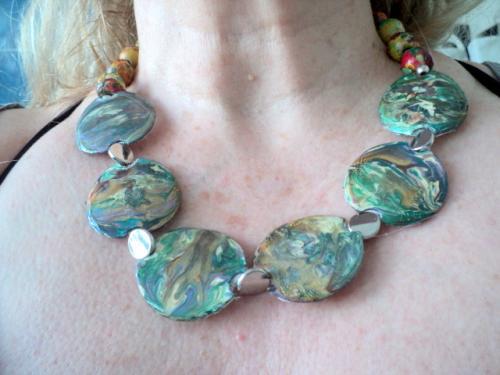 Collier composé de plaques rondes en plastique peint avec des peintures à effet,les plaques sont séparées entre elles par des perles plates  en métal argenté Le tout de cou et composé de perles en bois.