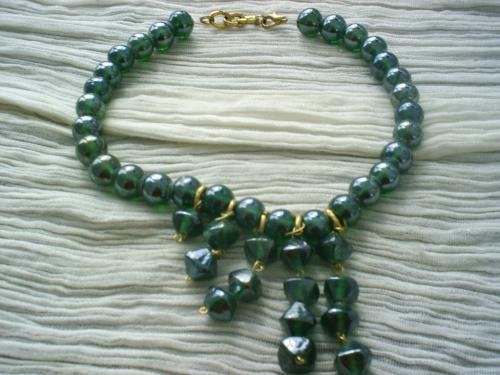 REGENCE: collier sur fil de nylon, le tour du cou est composé de perles rondes en verre de couleur vert irisé.5 branches de perles hexagonales,et de longueurs différentes pendent sur le devant. Les perles rondes d'où partent les cinq branches sont séparées par des anneaux dorés. Fermoir mousqueton, collier très élégant. Longueur 22 cm.