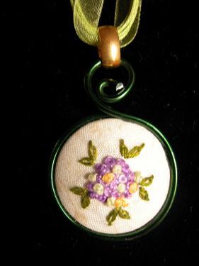 Collier avec médaillon brodé au point de noeuds et de bouclette, coloris jaune, vert et mauve , perle cirée en décor et lacet en coton ciré et organza. Diam 30mm