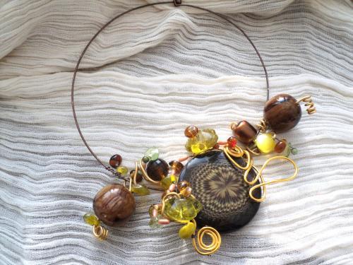 Tour de cou sur torque composé d'une grosse perle marron, de perles jaunes et marron en verre et en plastique. Le tout décoré d'un fil d'aluminium jaune.