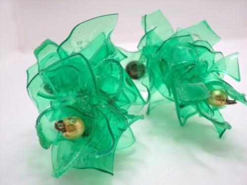 Boucles d'oreilles en chips de plastique vert superposés en quinconce, terminées par une perle de  nacre dorée. Le clou d'attache et en métal argenté.