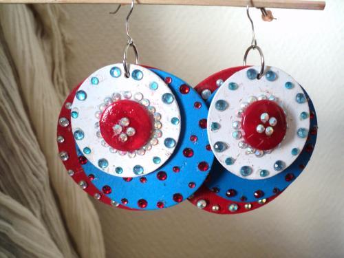 Boucles d'oreille pour oreilles perc�es,compos�es de trois disques en bois rouge bleu et blanc de trois tailles diff�rentes et d�cor�es avec des stass rouges,bleus et transparents