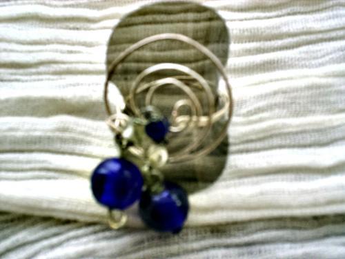GALAXIE: bague sur anneau en fil d'aluminium qui se continue pour former des cercles sur le dessus de la bague , décorées de perles bleues sur une chaînette.