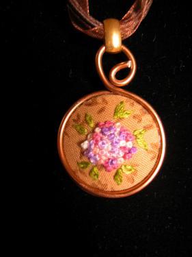 Collier avec médaillon brodé dans un dégradé de roses et mauves, lacet en coton ciré et organza. Diam 30mm