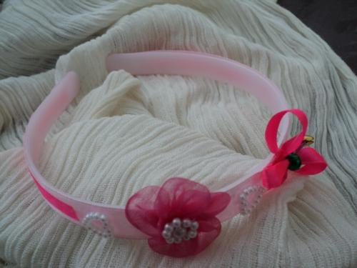 PRINTEMPS:Serre-tête en plastique rose pour petites filles.Le serre-tête est recouvert d'un ruban en satin rose pâle, il est décoré d'une fleur en tulle rose au coeur en perles blanches, deux coeurs en perles blanches se positionnent de chaque côté de la fleur. Des petites clochettes multicolores pendent à partir du coeur d'un gros noeud en satin rose fuchia, ce même ruban se trouve de chaque côté du serre-tête. Ce serre-tête ravira les petites filles par ses couleurs printanières et toutes ses petites décorations.