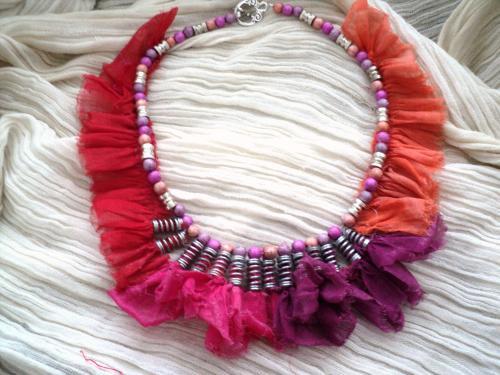 Tour de cou en tissus froncés orange,rouge,mauve,et rose qui sont encagés dans des petits ressorts; Le pourtour du collier est décoré de perles orange,rose et mauve.