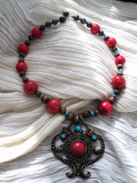 Collier compos� d'un superbe pendentif en bronze et d'un tour de cou en perles en bois rouge, bleue et marron.