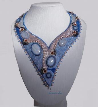 Un plastron ras-de-cou asymétrique avec plusieurs cabochons de calcédoine sertis par des délicas et des rocailles et entouré de perles