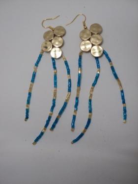 Boucles d'oreille fabriqu�es avec du fil de nylon,une estampe en m�tal dor�, et perles de rocaille bleue et dor�e