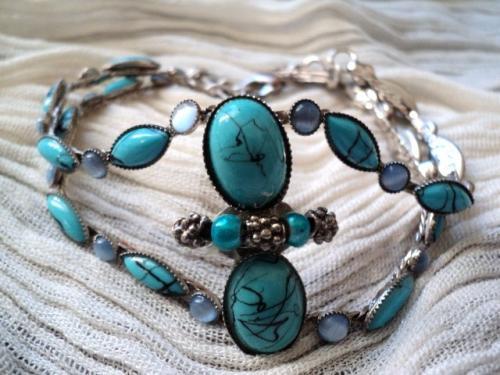 TURQUOISE: bracelet est composé de deux rangs de perles bleu turquoise et de perles bleu opaque, serties de métal argenté. Les deux bras sont séparés par deux grosses perles bleu turquoise et de petites perles en métal argenté. Le bracelet est fermé par une chaînette qui permet d'adapter le bracelet à toutes les tailles de poignet. Ce bracelet fait parti de la série des bijoux relookés. Les perles se trouvaient sur un sac. Ce bracelet est unique et original par son côté détourné.