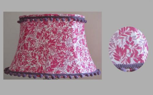 Abat-jour Pagode ovale confectionné dans un coton à fleurs rose doublé et agrémenté d'un galon de pompoms mauve.