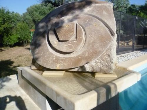 La sculpture posée sur le bac au dessus de la piscine.