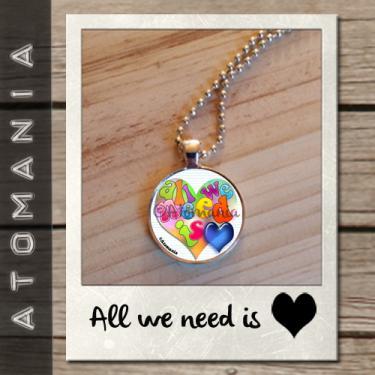 Pendentif « All we need is love» - ATOMANIA composé  d?une image créée par « Atomania », protégée par résine transparente, montage sur support argenté ? chaîne assortie (longueur : 60 cms). Format : 25 mm. Expédition sous huitaine après réception du paiement.