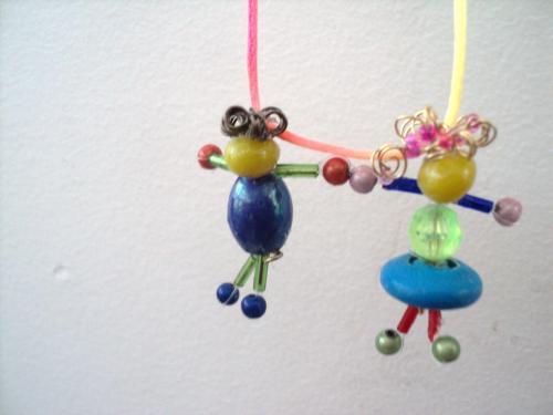 Collier compos� de deux pendentifs petit gar�on et petite fille en perles qui se tiennent la main et sont pendus � un cordon en tissu multicolore.Collier personnalisable