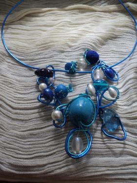 Collier en fil d'aluminium bleu et perles de toutes matières et différentes tailles bleues et blanches. Des perles en verre, en céramique,en bois,en tissus et des fleurs en verre. Collier réglable