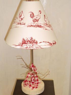 Lampe à poser réalisée sur un pied avec un socle en bois blanchi, sur tige chromée garni d'un petit ruban avec un petit fagot.   Abat-jour Conique réalisée avec un coton blanc aux décors de Poules effet