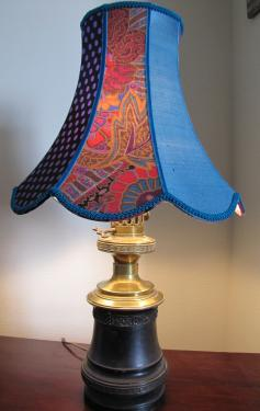 Nous avons associé cette ancienne lampe à pétrole en fonte et laiton à une pagode à festons aux tons très vifs confectionnée dans deux cotons anglais et une soie bleu de France. L'ensemble nous donne un air très Bohème.