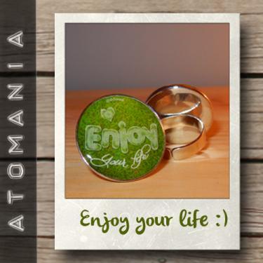 Bague « Enjoy your life » - ATOMANIA composée d?une image créée par « Atomania », protégée par résine transparente, montage sur support de bague bronze réglable. Format : 25 mm. Expédition sous huitaine après réception du paiement.
