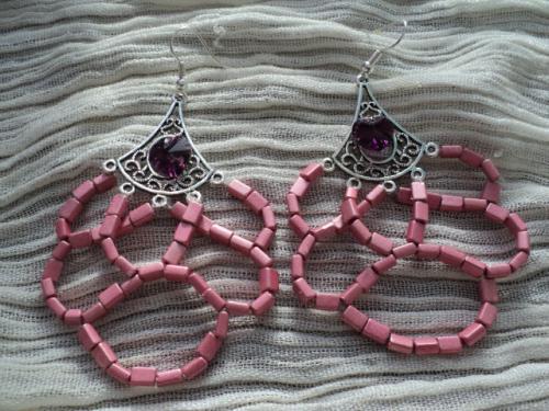 SARAH:Boucles d'oreilles pour oreilles percées, composées d'estampes en métal argenté décorées de coeurs mauve en cristal de swaroski, et de pendants de perles roses en métal. Les crochets sont en métal argenté traité.
