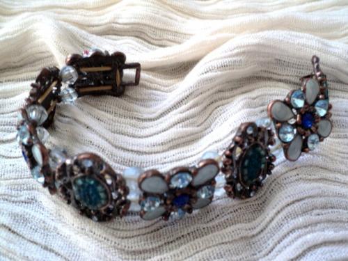 FLEUR:bracelet composé de huit plaques différemment décorées mais toutes avec des perles bleues, rocaille,strass,perles en céramiques....Elles sont séparées par des facettes bleu clair