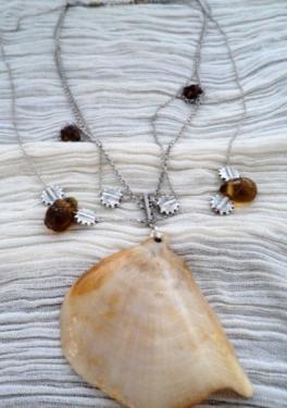 Coquillage verni et attaché a des chaînes très fines auxquelles sont accrochées des perles goutte en verre ambre, deux strass et des perles rondes en métal argenté.
