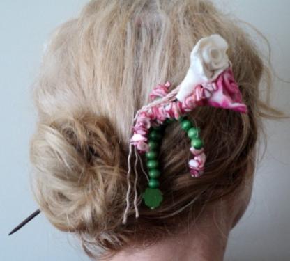 BOUQUET FLEURI:Pic à cheveux sur pic en bois peint en noir et verni. Le haut du pic est composé de deux fleurs en pâte fimo rose et blanche.De ces deux fleurs descendent un galon rose des perles vertes en bois et des chips rose marbré