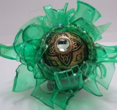 Bague entièrement fabriquée avec des matériaux recyclés:chips de plastique, vieux bouton surmonté d'un strass,et l'anneau,une ancienne bague en pâte fimo;le tout est collé et des facettes vertes entourent la base du bouton