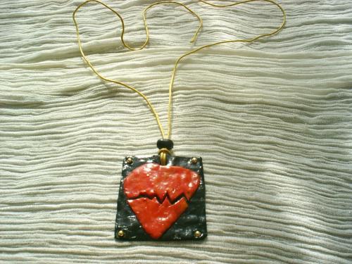COEUR BRISE: Pendentif en pâte fimo noire décoré par un coeur en pâte fimo rouge cassé en son milieu, à chaque coin une petite perle en métal doré le tout verni. Lien en coton jaune.