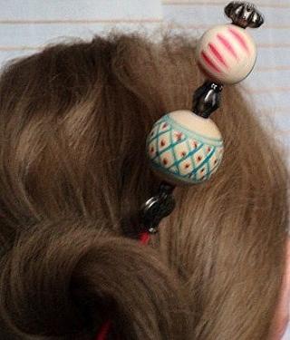 TANZANIE:Pic à cheveux sur tige en bois peint en rouge et verni, décoré de perles africaines en bois, séparées par des perles en métal argenté. Très léger