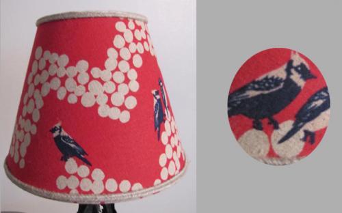 Abat-jour de forme conique habillé d'un tissu en lin avec des oiseaux bleus sur un fonds couleur rose indien. Une soutache en lin rehausse ce modèle.