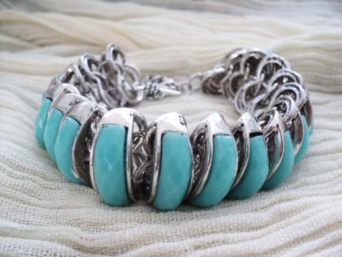 Bracelet en métal argenté composé de maillons et de cabochons bleus adaptable à toutes tailles de poignet.