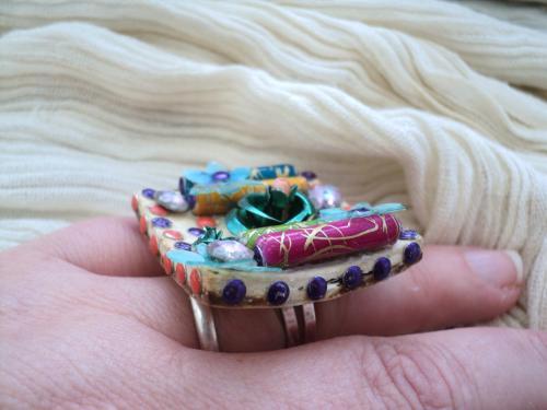 bague sur un anneau en métal argenté et plateau bouton en cuir sur lequel une fleur en métal vert est entouré de 4 perles tube en porcelaine  et de deux fleurs n plastique et une petite en métal vert le tout décoré par des strass mauve et orange