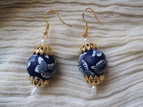 Boucles d'oreille compos� de deux perles en caoutchouc bleues avec des fleurs blanches,enserr�es entre des estampes dor�es, et accroch�es avec une perle nacr�e un crochet dor�