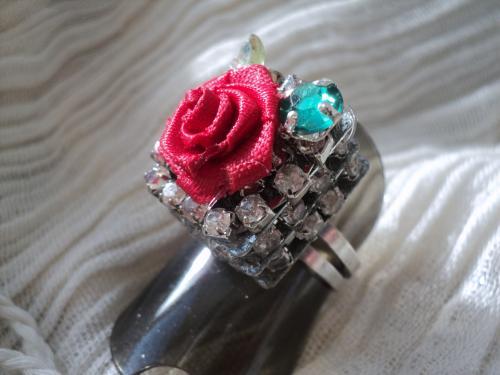 Bague réglable avec un anneau en métal argenté surmonté de trois étages de strass blancs, une fleur en tissus rouge et un strass vert