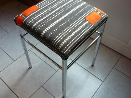 Tabouret initialement recouvert de skaï brun, refait (sanglage mousse et toiles) et  recouvert d'un tissu neuf pointillets noirs et beiges-aux-points-d'exclamation oranges.