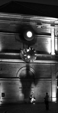 En 2010, l?atelier Utinam Besançon prend une nouvelle dimension et passe de l?infiniment petit au géant. En l?occurrence une première oeuvre horlogère monumentale imaginée et réalisée par notre explorateur du temps pour compter à rebours les heures et les jours qui séparent sa pose de la mise en ligne du nouveau TGV Rhin-Rhône, soit un an. Installée sur le fronton du Musée des Beaux Arts, une horloge à balancier surmontée d?un dispositif lumineux qui bât au rythme cardiaque et fait écho (annonciateur) au concept de «La Matrice», l?horloge de la nouvelle gare TGV. Les aiguilles tournent tous les quarts d?heure, s?emballent en sens «senestre» pour décrire un mouvement qui accompagne le balancier dans une course folle où le temps s?échappe un instant... Elles tournent 12 heures à l?envers en 2 minutes puis reprennent le cours du temps. Sur la commande de la Région Franche-Comté, et sous la direction de Philippe Lebru, onze entreprises franc-comtoises ont pris part à cette aventure magistrale.