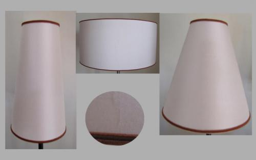 Deux abat-jours coniques et une suspension en soie blanc cassé  et  rehaussés du même galon couleur chaudron donne une harmonie à l'ensemble et souligne la sobriété du lieu.