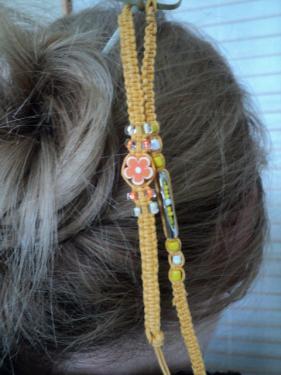 TRANCHE D'ORANGE:Pic à cheveux composé d'un pic en bois sur le quel partent deux liens en macramé en fil de coton orange.L'un est décoré par une fleur en plastique ainsi que de petites perles blanches et orange, l'autre est décoré de perles blanches et jaune de tailles différentes